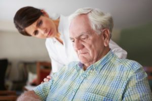 A woman carer concerned about an elderly man looking depressed